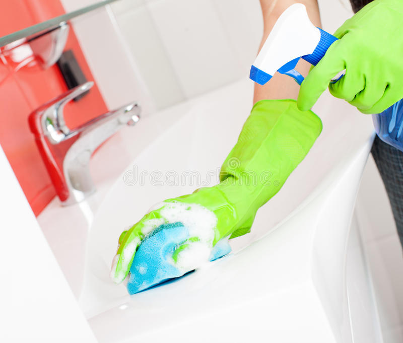 Woman cleaning sink and faucet. In bathroom at home stock photography