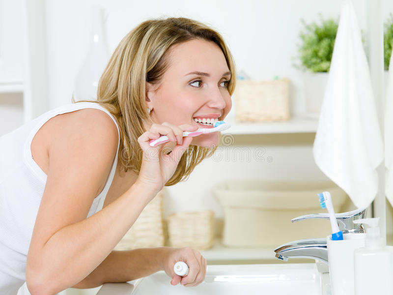 Woman cleaning teeth with toothbrush royalty free stock photography