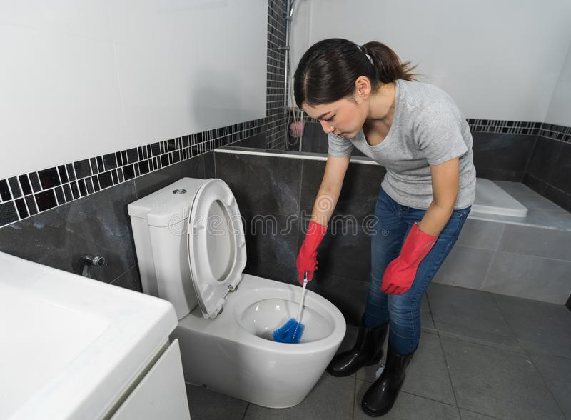 Woman cleaning toilet bowl with brush stock images