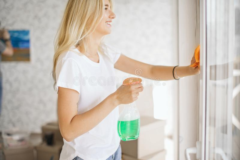 Woman cleaning window at new home after moving, her husband hanging picture on background royalty free stock image