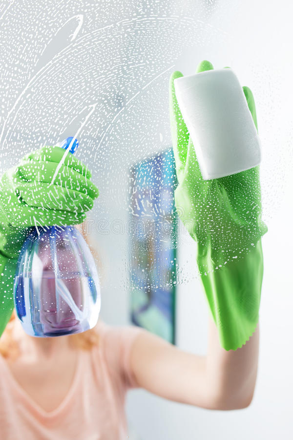 Woman cleaning window pane with detergent, cleaning concept stock photo