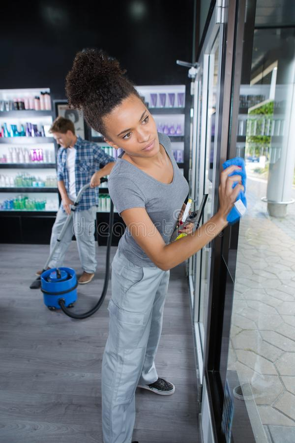 Woman cleaning window with rag and cleanser spray at salon royalty free stock photo