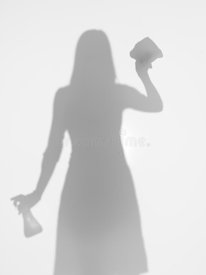 Woman cleaning a window, silhouette stock image