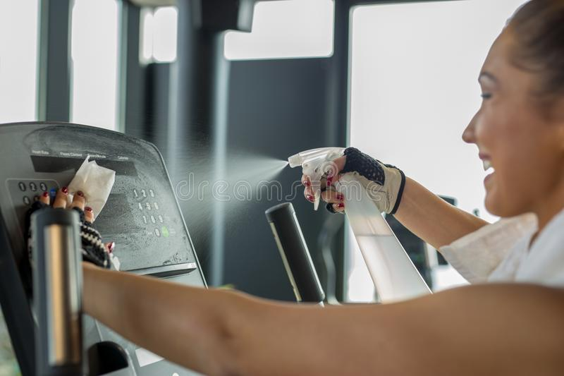 Woman cleaning work out area at the gym stock images