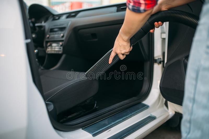Woman cleans car interior with vacuum cleaner. Carwash. Lady with hoover on self-service automobile washing. Outdoor vehicle cleaning royalty free stock photos