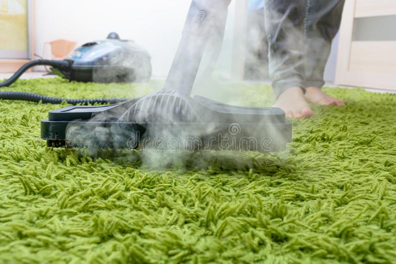 Woman cleans a carpet with a steam cleaning. royalty free stock photo