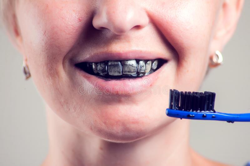 Woman cleans teeth with charcoal toothpaste. People and healthcare concept. Woman cleans her teeth with charcoal toothpaste. People and healthcare concept royalty free stock image