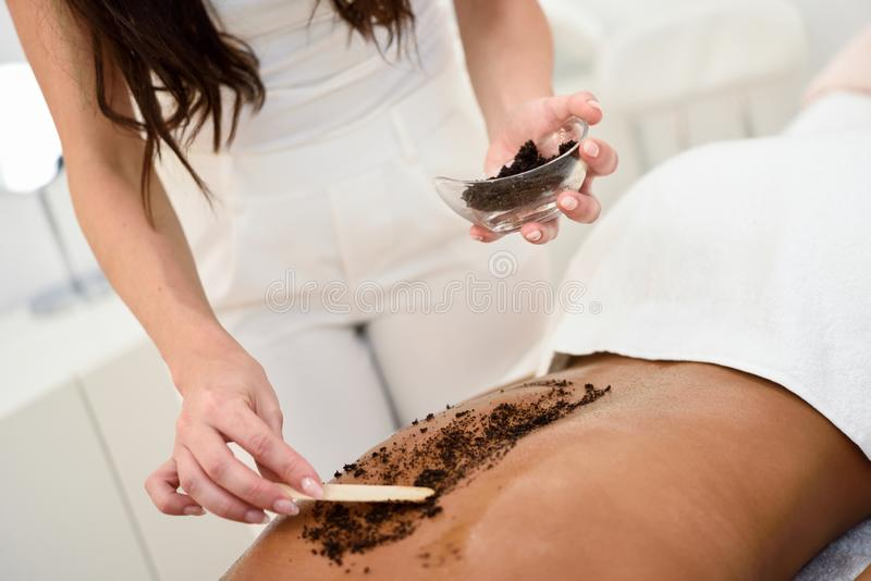Woman cleans skin of the body with coffee scrub in spa wellness royalty free stock photography