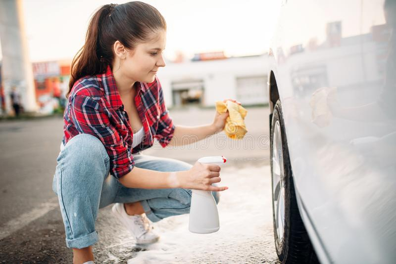Woman cleans wheel disk of the car with spray stock photography