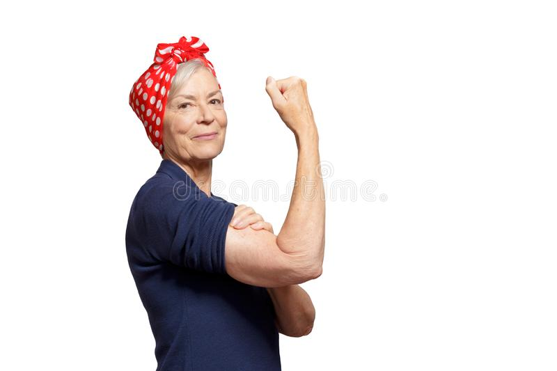 Woman clenched fist isolated copyspace. Self-confident senior woman with a clenched fist rolling up her sleeve, isolated on white, copyspace royalty free stock images