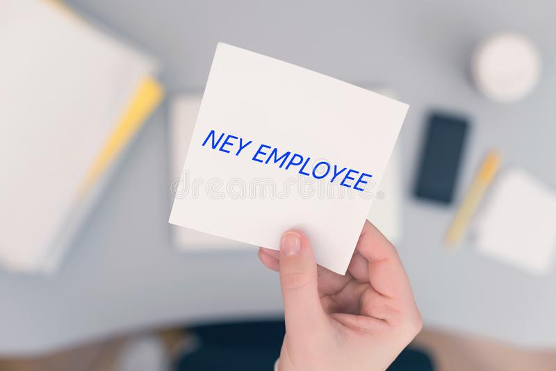 Woman clerk sitting holding note paper sticker with new employee phrase. Business concept. Concept stock photography