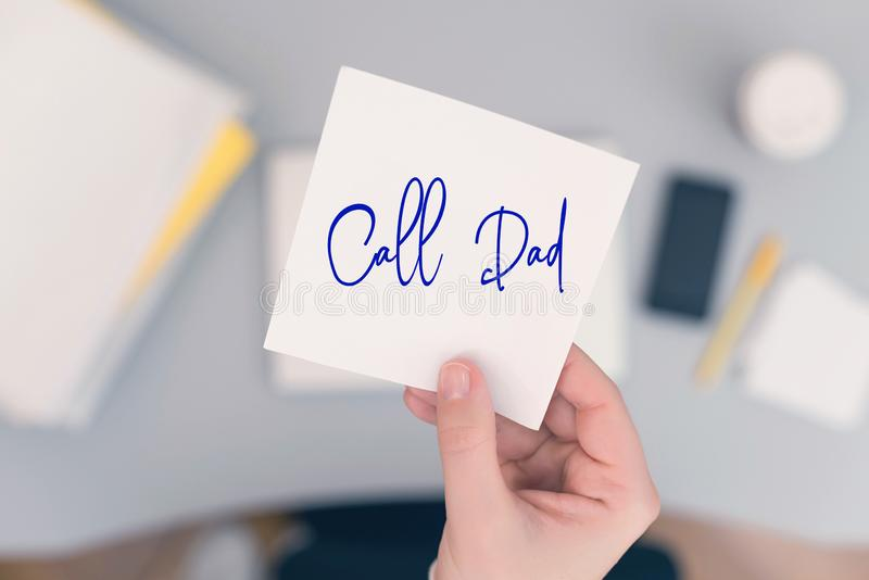 Woman clerk is sitting at office table holding note sticker with message call dad.  royalty free stock photo
