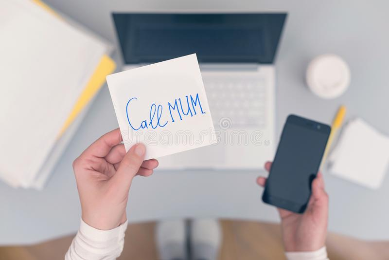 Woman clerk is sitting at office table holding note sticker with message call mum. Woman clerk is sitting at office table holding note sticker with message `call royalty free stock photos