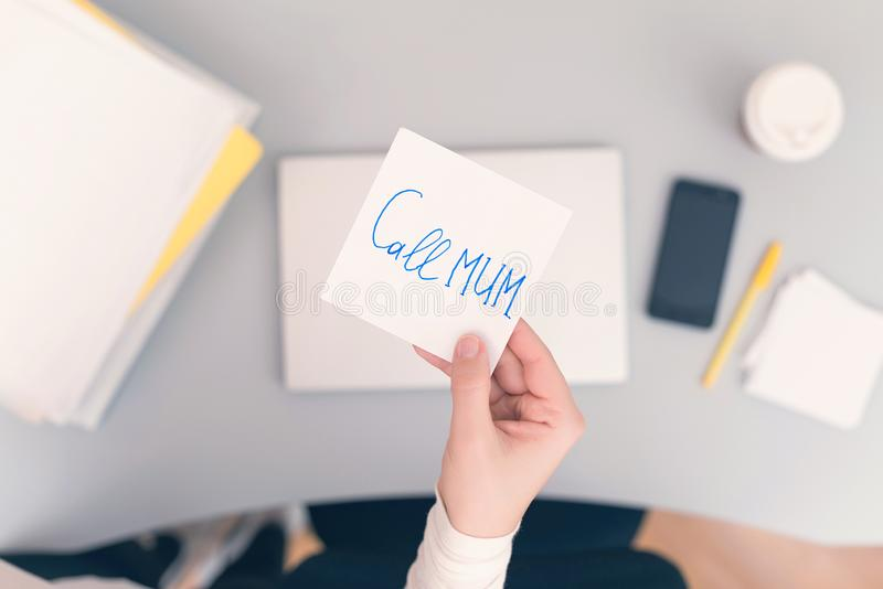 Woman clerk is sitting at office table holding note sticker with message call mum. Woman clerk is sitting at office table holding note sticker with message `call stock image