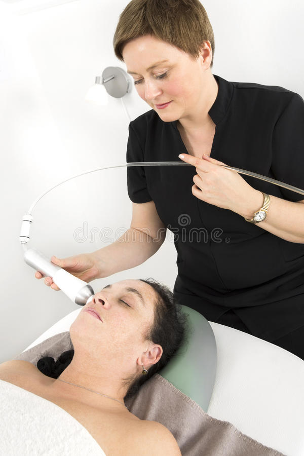 Woman client gets face slimming treatment at beauty clinic stock image