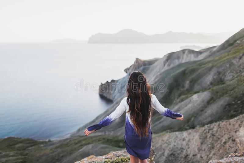 Woman on cliff with stunning view of sea coast with hills and mountains. Woman standing on a cliff with a stunning view of sea coast with background of the hills stock photos