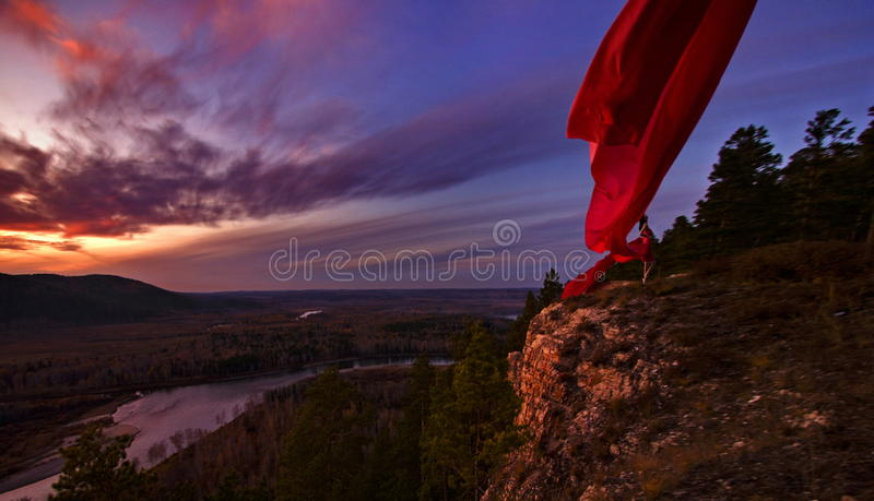 Woman on cliff at sunset