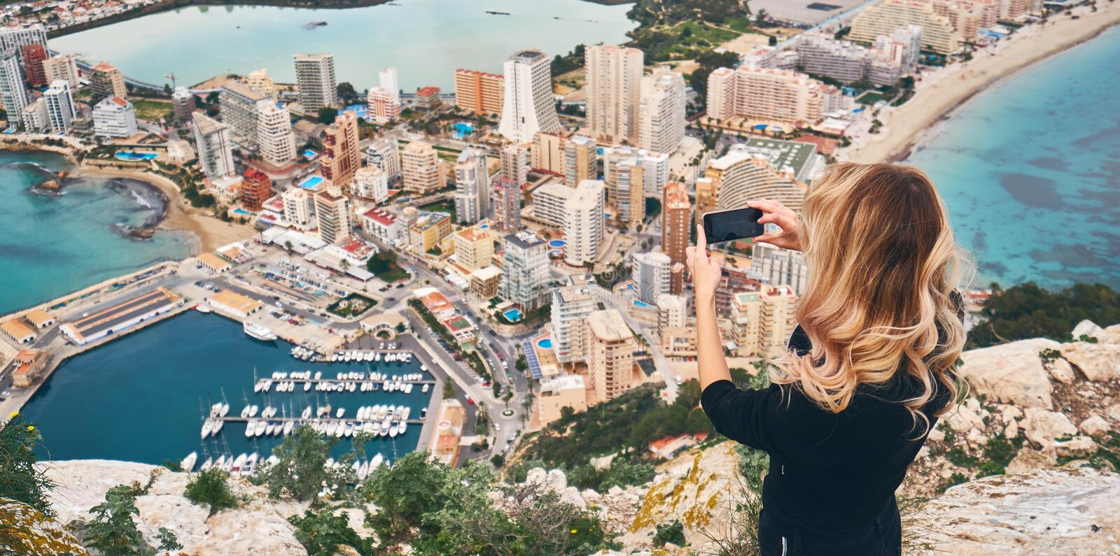 Woman climbed up on Penon de Ifach rock. Enjoy view of city from top, stand on peak of mountain takes photo of cityscape and stock photography