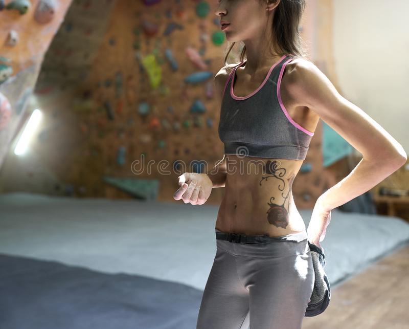 Woman climber is chalking hands with white chalk powder before climb in indoor climbing gym. woman getting ready to. Woman climber is chalking hands with white stock photo