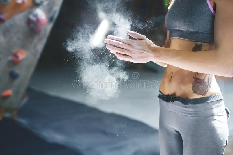 Woman climber is chalking hands with white chalk powder before climb in indoor climbing gym. woman getting ready to. Closeup view of woman climber is chalking stock photo