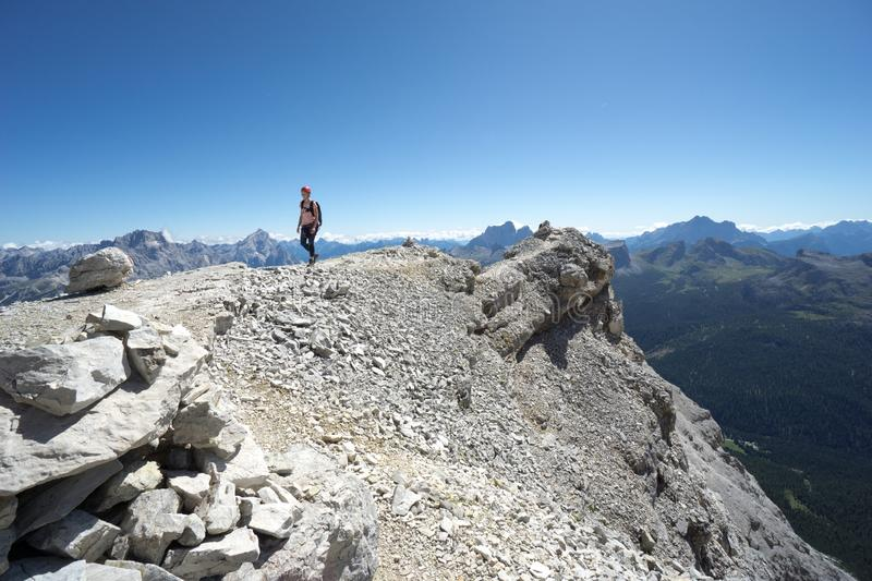 Woman climber hiking along a rocky summit ridge in the Dolomites of Italy royalty free stock images