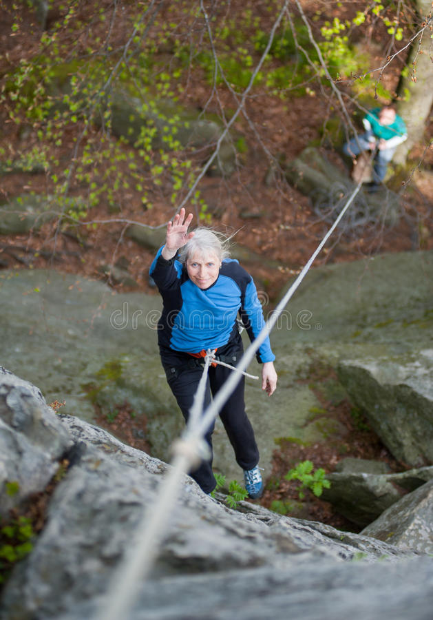 Woman with climbing equipment. Hanging on a rope and waving at the rock in the mountains. Another men insures on the ground royalty free stock photos