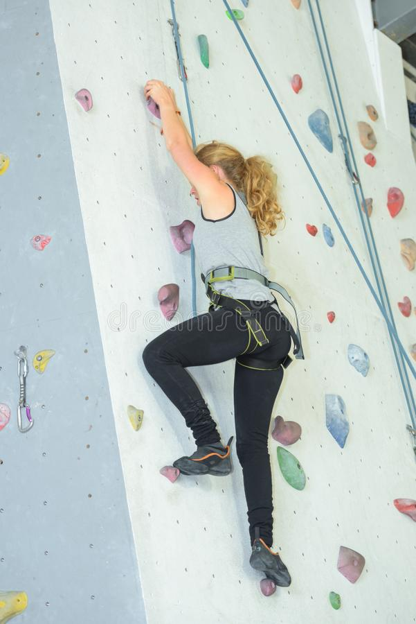 Woman climbing indoor wall royalty free stock photography