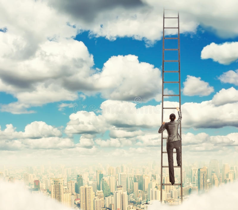 Woman climbing the ladder royalty free stock photo