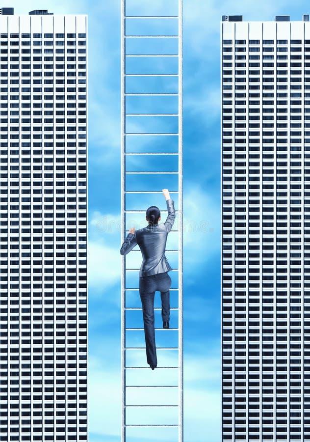 Woman climbing the ladder stock photo