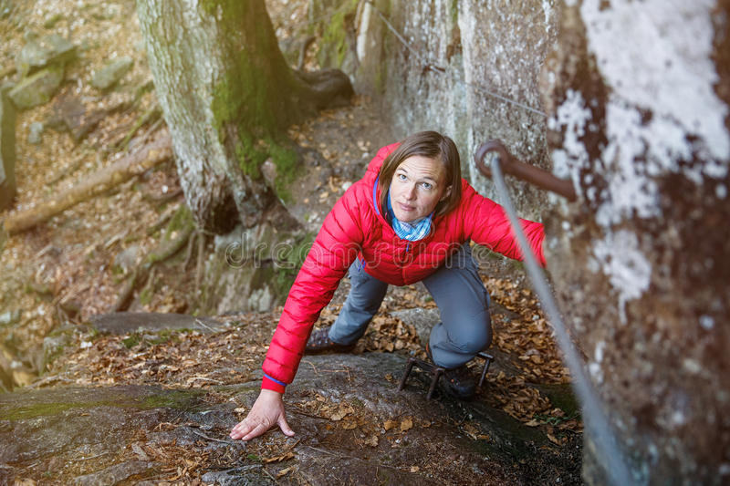 Woman climbing rock, holding security railing. Woman climbing rock in the forest, holding security railing, ascending to the top, succeeding. Active lifestyle royalty free stock images