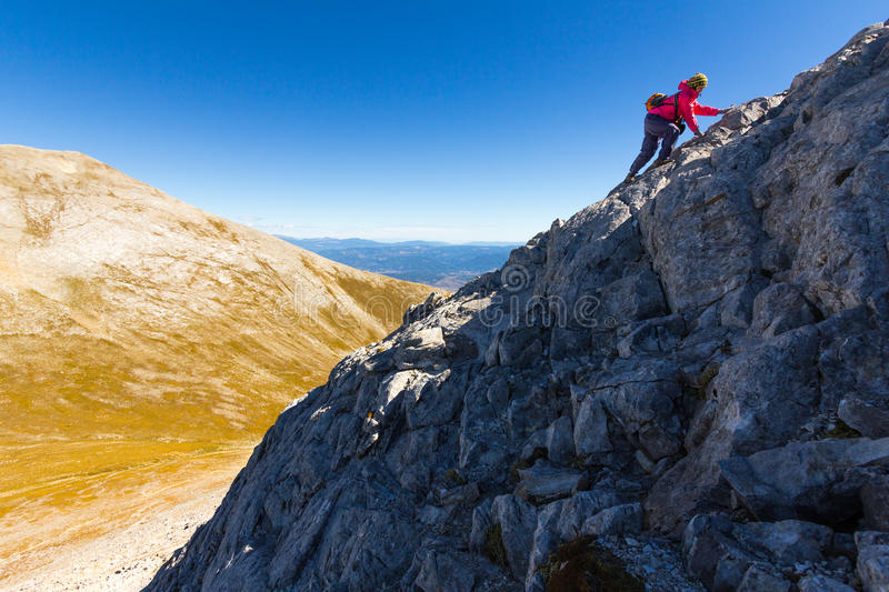 Woman climbing steep mountain slope. Woman mountaineer climbing steep rock mountain slope. Vihren, Pirin mountains, Bulgaria royalty free stock image