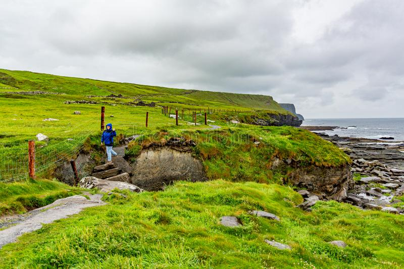 Woman climbing a stone ladder on a rainy day on the coastal walk route from Doolin to Cliffs of the Moher. Geosites and geopark, Wild Atlantic Way, spring day stock images