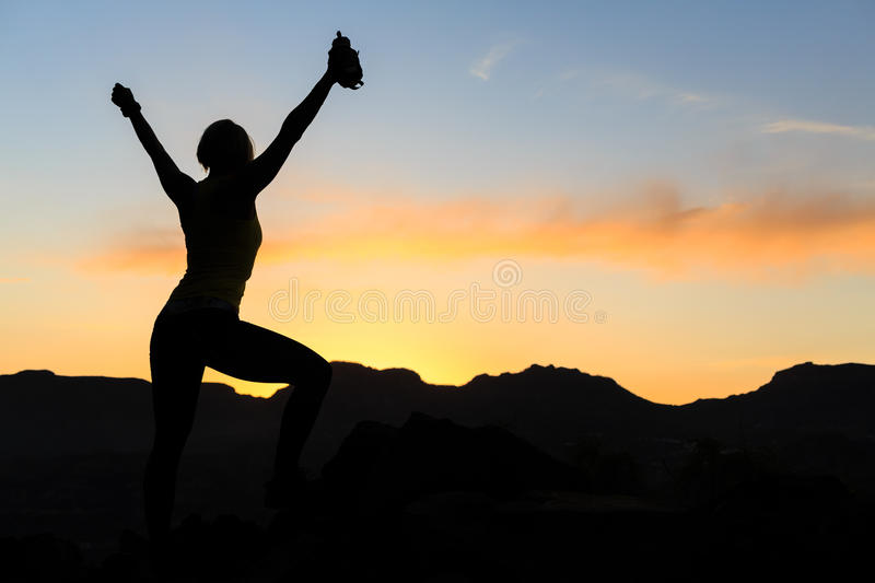 Woman climbing success silhouette in mountains sunset stock photo