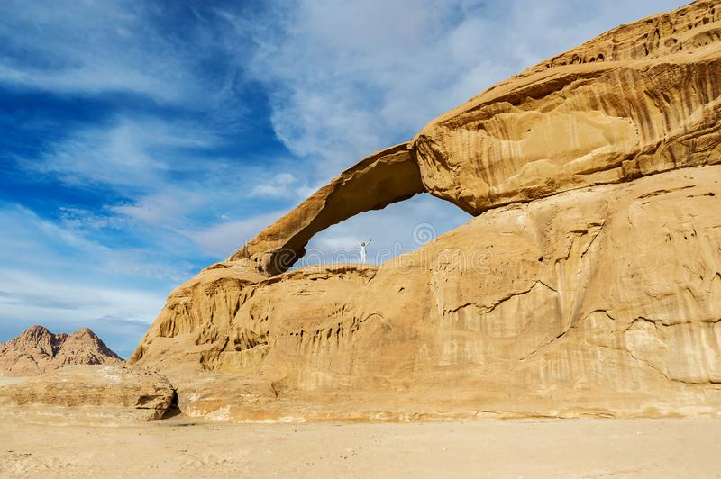 Woman climbing to the Burdah rock bridge in Wadi Rum desert stock photography