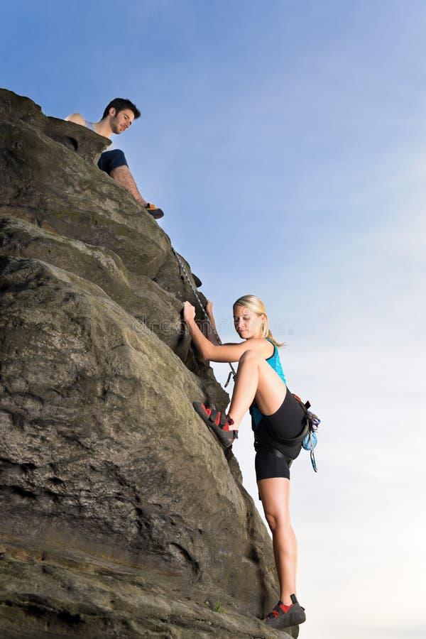 Woman climbing up rock man hold rope royalty free stock photo