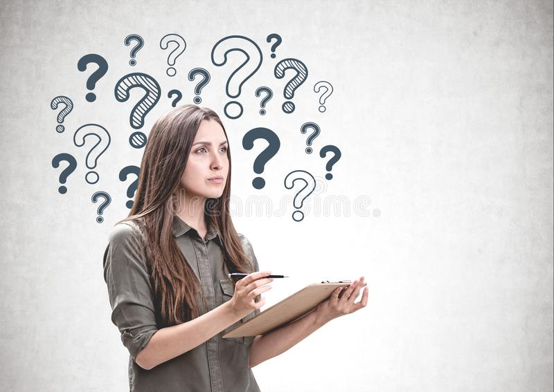 Woman with clipboard, question marks royalty free stock images
