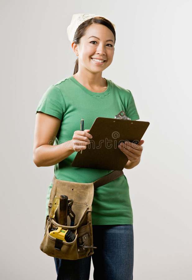 Woman with clipboard and tool belt. Self-sufficient woman with clipboard and tool belt stock photo
