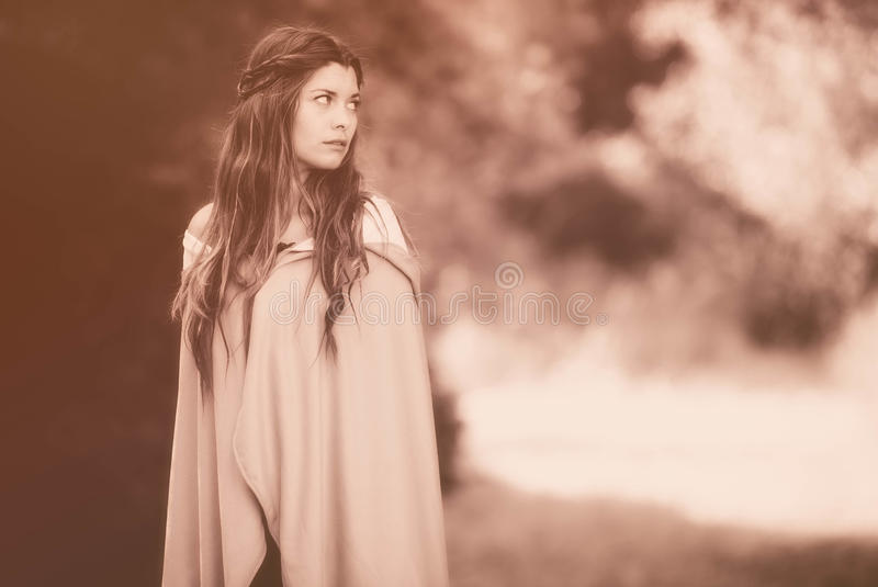 Woman in cloak. Fantasy woman in cloak in sepia colour stock photo
