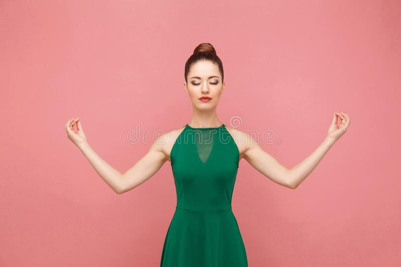 Woman closed eyes, doing meditation, mudram peace. Expression emotion and feelings concept. Studio shot, on pink background stock image