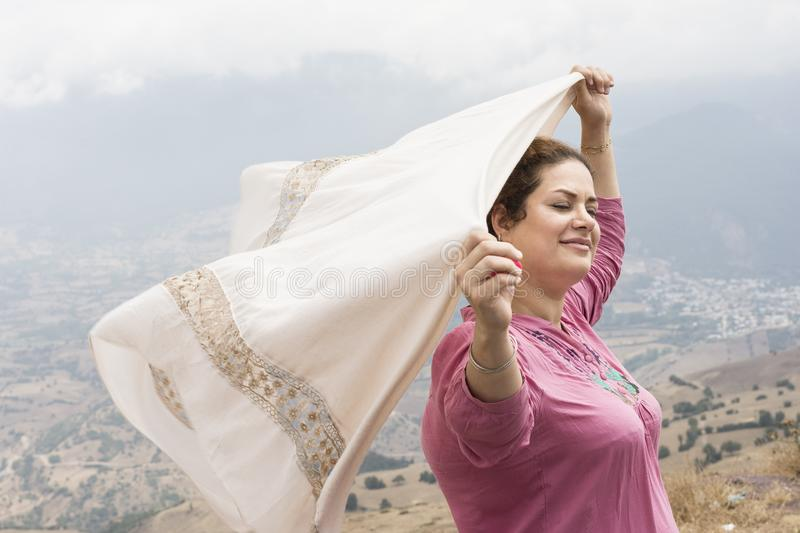 Woman with closed eyes holding a scarf in hands in natuer and en stock images