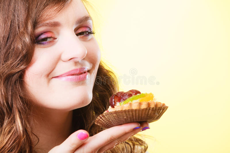 Woman closed eyes holds cake in hand stock photos