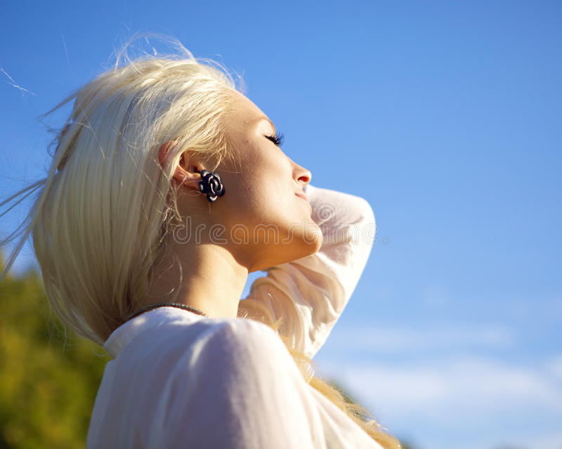 Woman with closed eyes relaxing in sun stock image