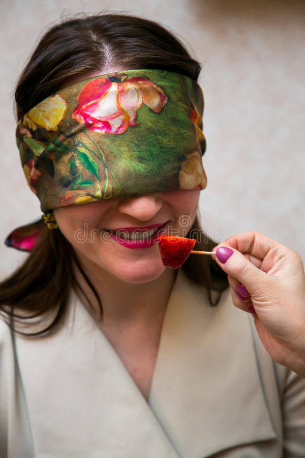 Woman with closed eyes sniffs strawberry stock photography