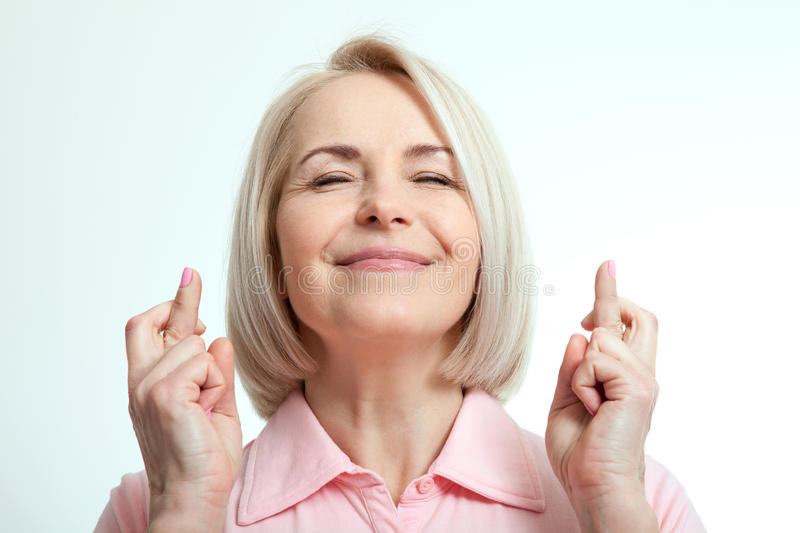 Woman closed her eyes, make a wish and crossed fingers. stock images