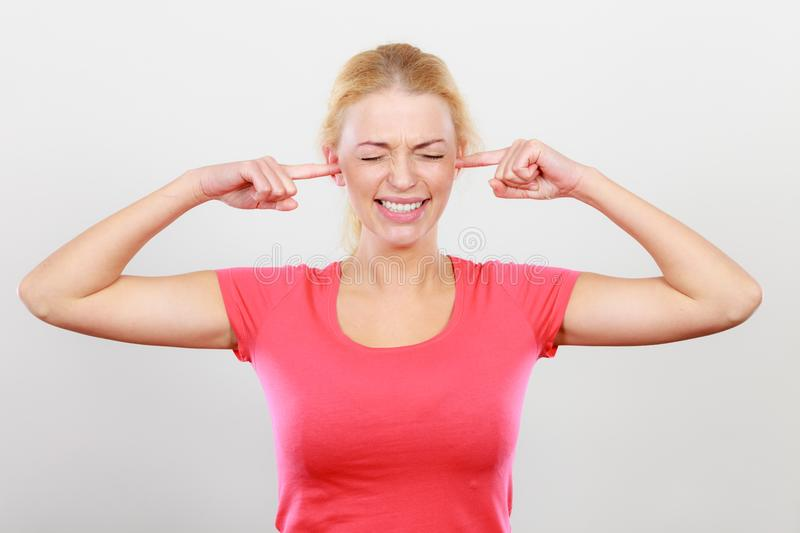 Woman closing her ears with fingers. Unhappy blonde woman closing her ears with fingers. Too loud environment, face expression concept royalty free stock photography