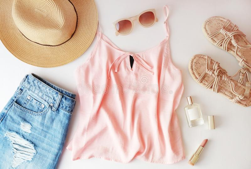 Woman clothes and accessories: pink top, jeans skirt, perfume, sandals, sunglasses, hat, lipstick on white background. Flat lay tr stock photography