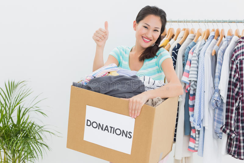 Woman with clothes donation gesturing thumbs up royalty free stock photos