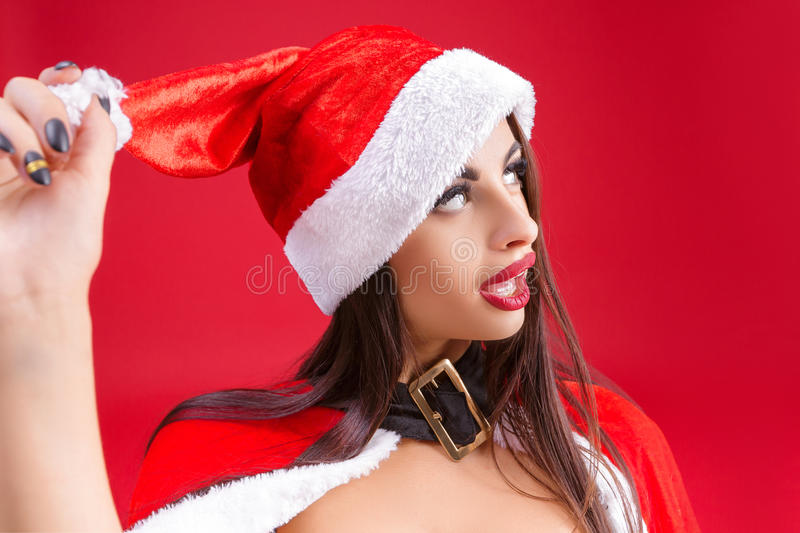 Woman in clothes of Santa Claus red background. cartoon. Woman in clothes of Santa Claus clown and fooling around on a red background. cartoon stock photo