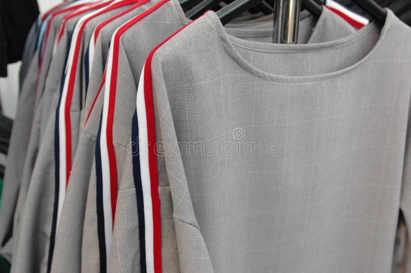 Woman clothes on a stand in a department store. Clothing and fashion, retail, textile, shop, style, t-shirt, apparel, casual, wear, design, dress, assortment stock images