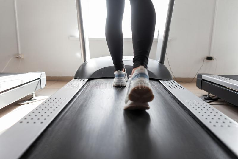 Woman coach trains on a treadmill in a gym. Girl runs on a treadmill. Sports exercises for weight loss. Rear view of female legs royalty free stock photography